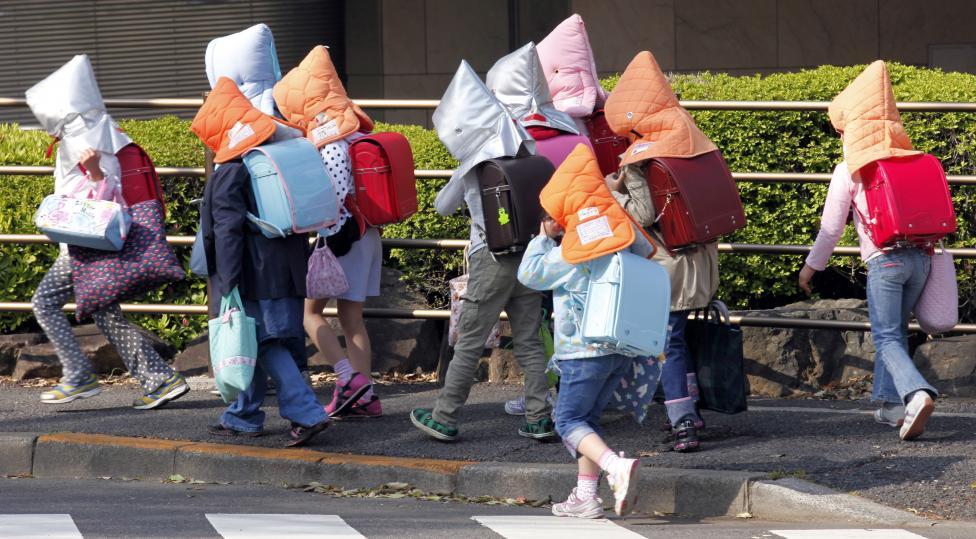 Elementary schoolchildren wear protective headgear as they walk to school in Tokyo, April 25, 2011.   REUTERS/Kim Kyung-Hoon